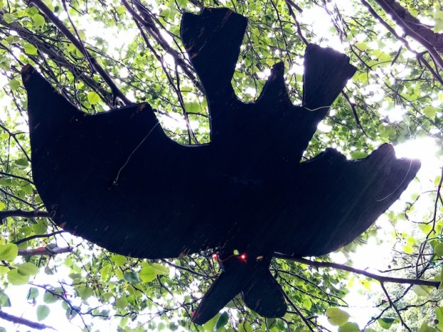 large wooden bat hanging from a tree