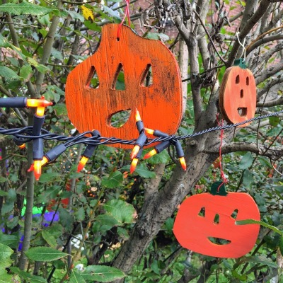 wooden Jack-o-lantern ornaments hanging from tree limbs