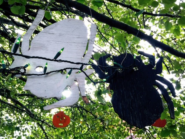 two wooden spider ornaments hanging in a tree