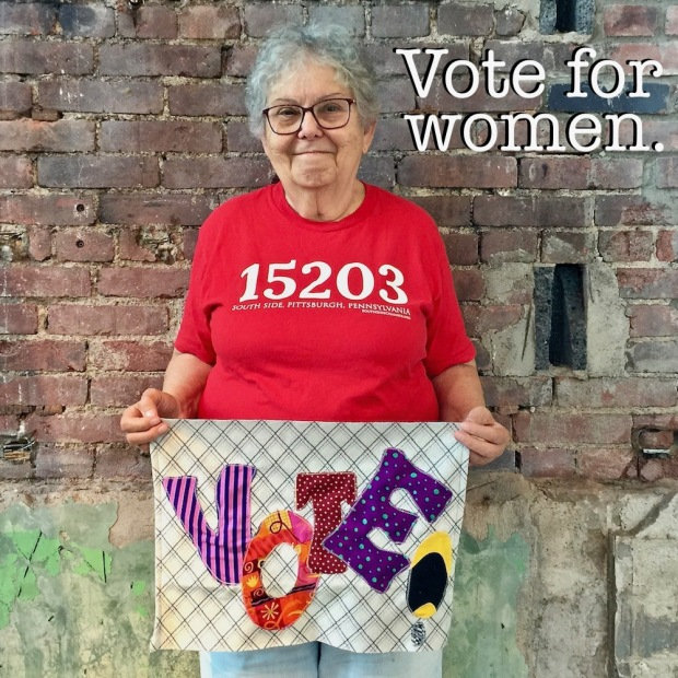 "woman holding handmade fabric ""Vote"" sign"
