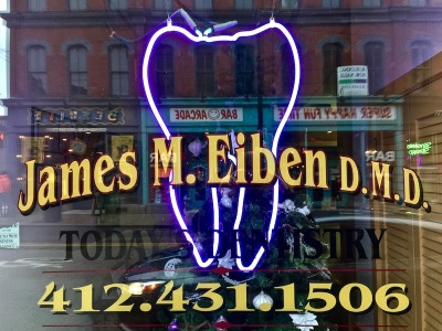 front window for dentist James M. Eiben with large neon tooth