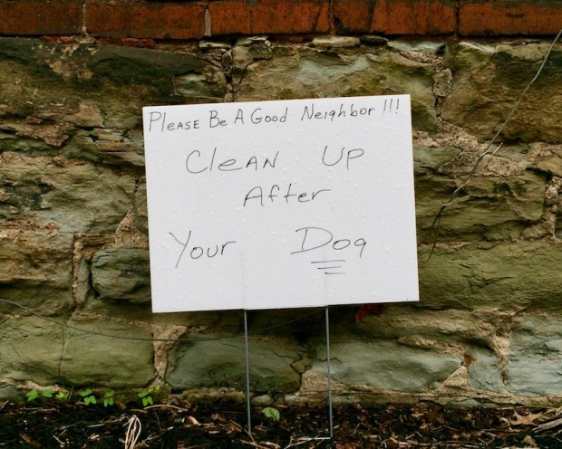 """handmade yard sign reading """"Please be a good neighbor!!! Clean up after your dog"""""""