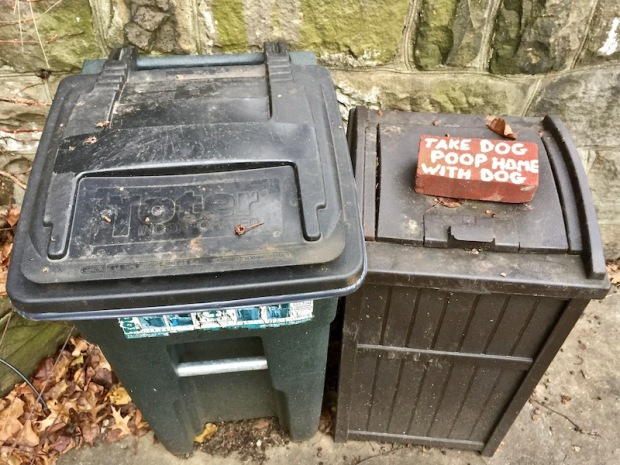 """brick painted with message """"Take dog poop home with dog"""" on outside garbage bins"""