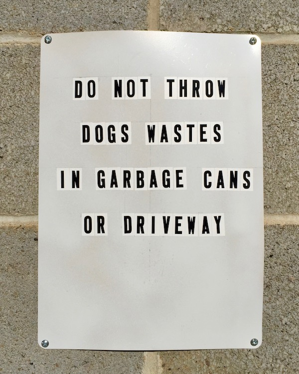 """Sign posted on garage wall reading """"Do not throw dogs wastes in garbage cans or driveway,"""""""
