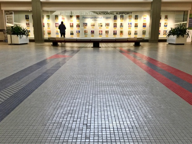 Passenger Portrait Project installed in glass case at Pittsburgh International Airport