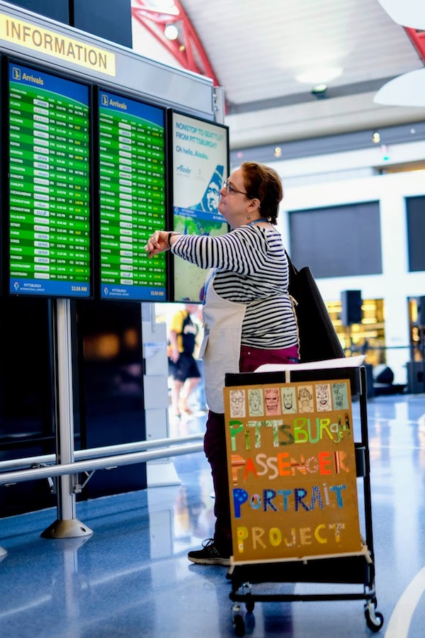 artist Kirsten Ervin looking at Pittsburgh airport's arrival information board