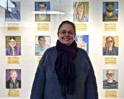 Artist Kirsten Ervin in front of chalk pastel portraits of airport passengers