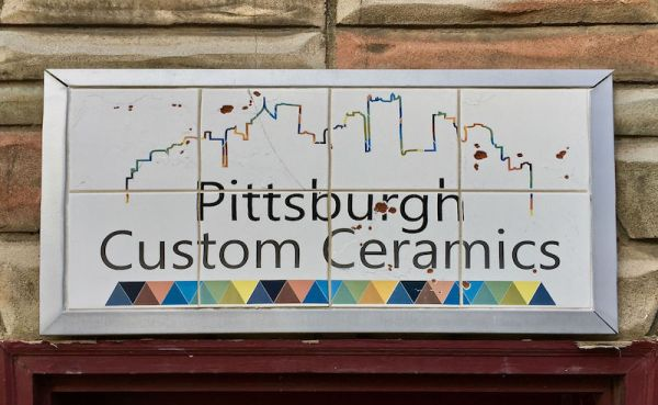 retail store sign for Pittsburgh Custom Ceramics with outline of Pittsburgh's skyline