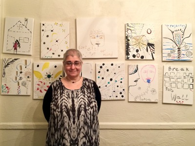 artist Parvaneh Torkamani with wall of paintings