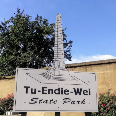 sign for Tu-Endie-Wei State Park in Point Pleasant, WV featuring large cut-out model of stone monument