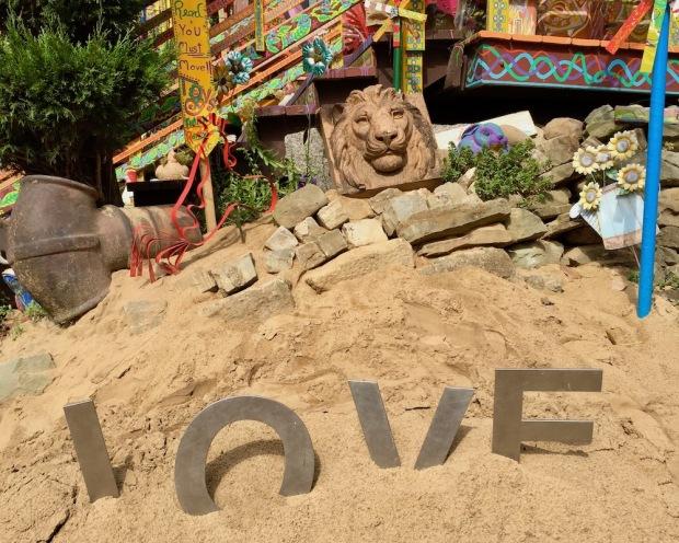 metal letters spelling L-O-V-E in sand at Randyland