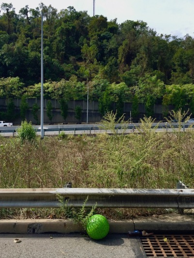 green play ball on the curb of highway
