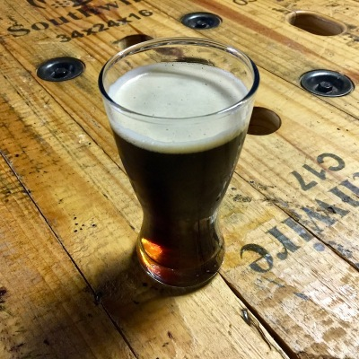 dark beer in glass on rough wooden table
