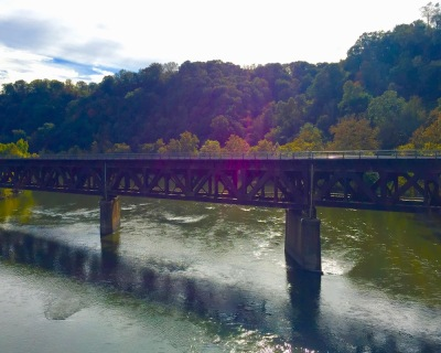 river, trees in fall colors, and train bridge in Western PA