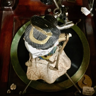 ceramic and textile dancing puppet attached to spinning center of a Victrola at DeBence Antique Music World