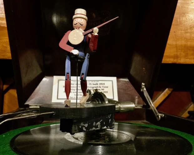 wooden dancing puppet attached to spinning center of a Victrola at DeBence Antique Music World