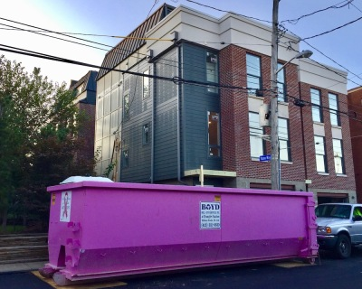 large dumpster painted bright pink in front of apartment building