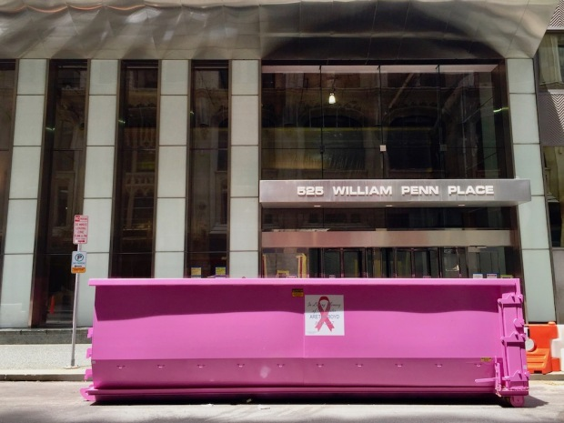 large dumpster painted bright pink in front of office building