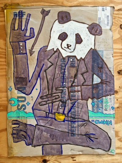 street art painting of polar bear in a brown dress suit on cardboard