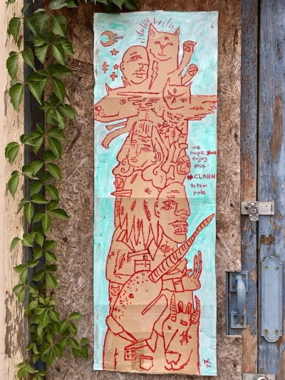 street art painting of totem pole of various animals on cardboard