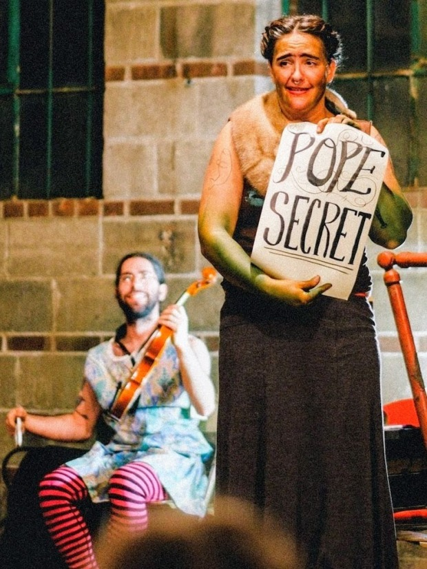 """actress in robes with sign reading """"Pope Secret"""""""