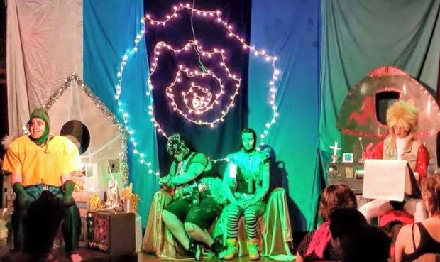 group scene from play with actors against colorful handmade stage set