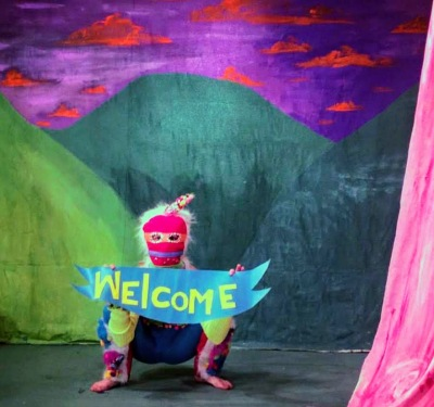 "costumed character with ""Welcome"" sign"
