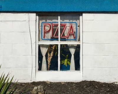 "basement window with neon ""PIZZA"" sign"