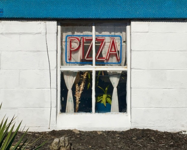"""basement window with neon """"PIZZA"""" sign"""