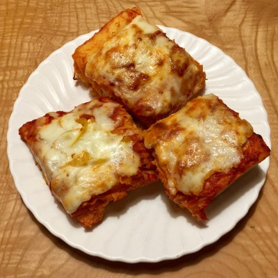 three rectangular slices of pizza on a white plate