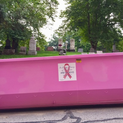 pink breast cancer awareness dumpster in front of cemetery