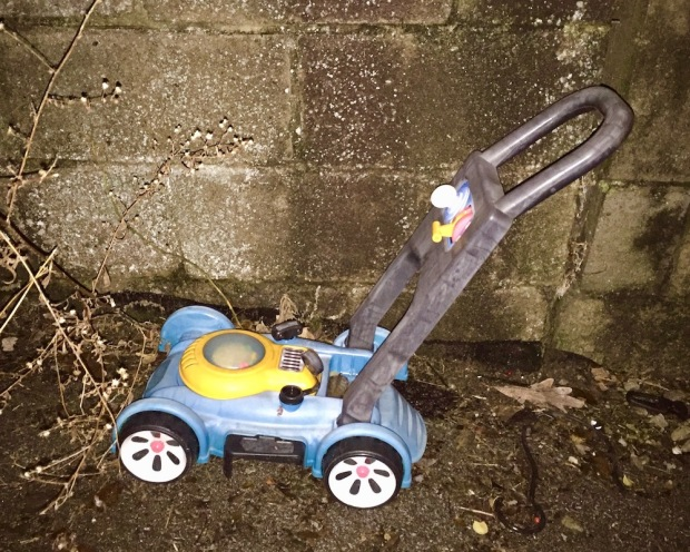 toy lawnmower left in alley