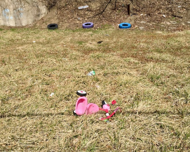 pink tricycle abandoned in grassy lot