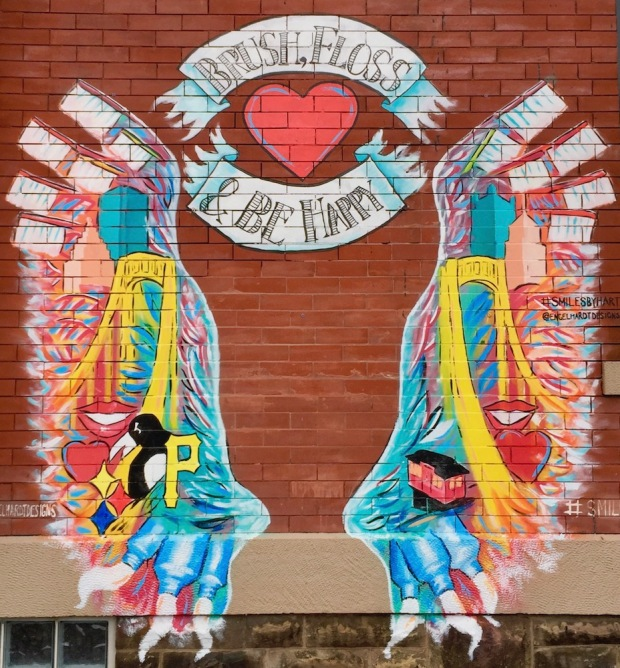 """mural painted on brick wall for Smiles by Hart dentist office including Pittsburgh imagery, toothbrushes, toothpaste, and the banner message """"Brush, Floss & Be Happy"""""""
