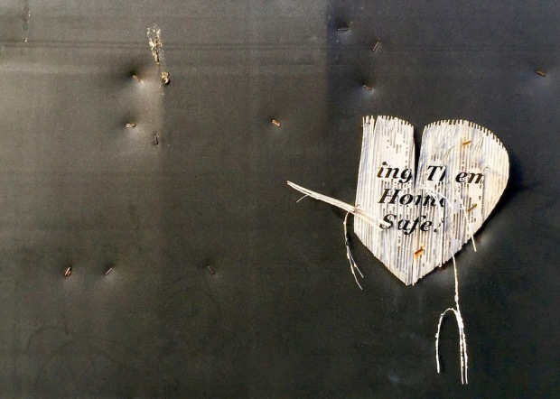 deteriorated paper heart stapled to black wall