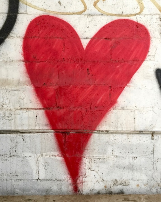 large red heart painted on cinderblock wall