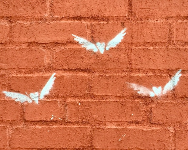 stencil images of hearts with wings on brick wall
