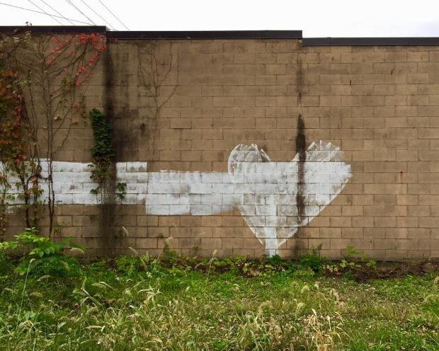 graffiti painted heart on cinderblock wall