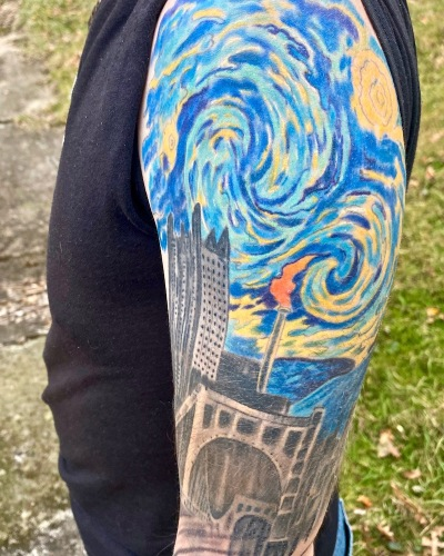 Monessen mayor Matt Shorraw's tattooed arm including image combining downtown Pittsburgh with flaming smokestack of Monessen