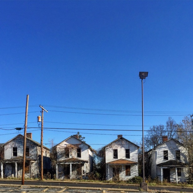 row of identical wooden houses, all missing windows and overgrown with weeds