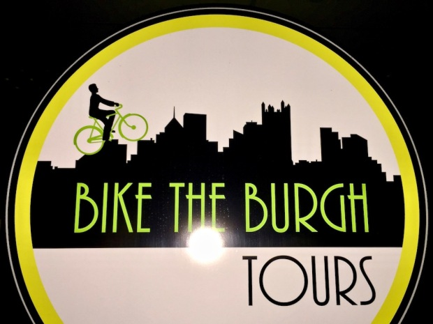 sign for Bike the Burgh Tours with a bicycle rider on a silhouette of the Pittsburgh skyline