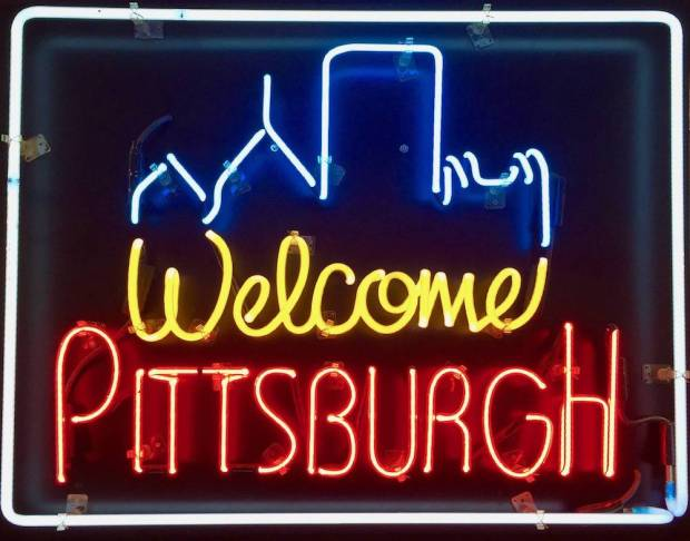 neon sign for Welcome Pittsburgh including part of the downtown skyline