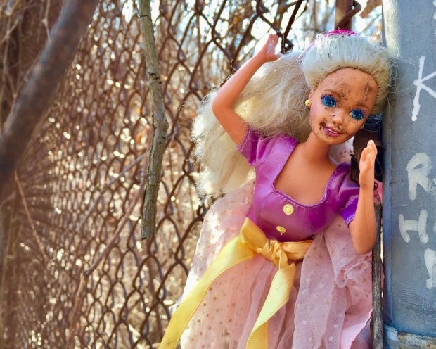 Barbie doll attached to chain link fence