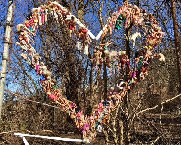 large number of Barbie dolls hung on a chain link fence in the shape of a heart