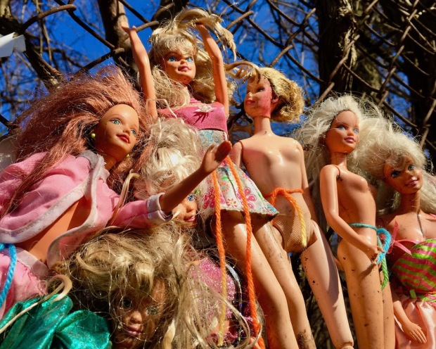 collection of Barbie dolls displayed on chain link fence in the sunshine