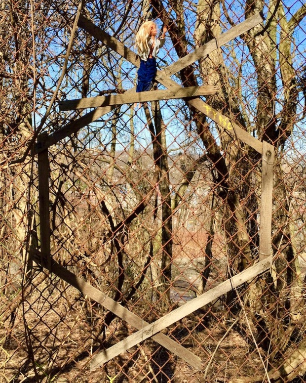 Barbie doll attached to chain link fence with wooden hex symbol