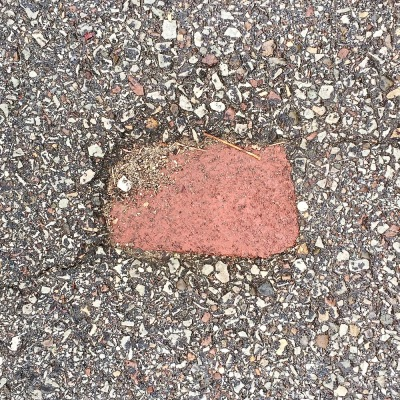 brick embedded in road tar