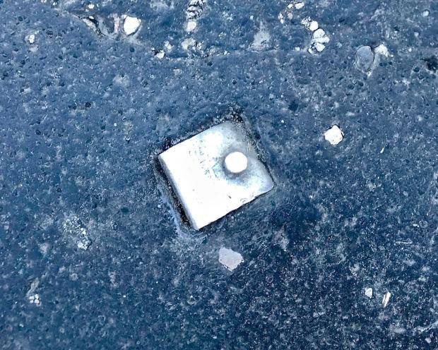 metal bracket embedded in road tar