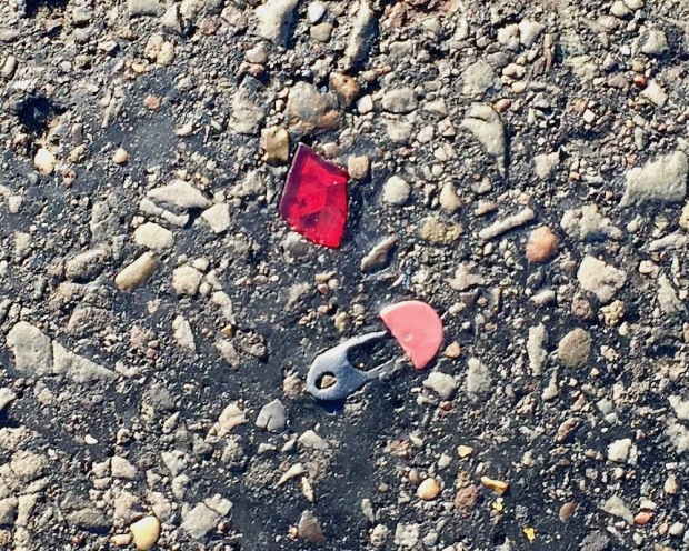 broken reflector and metal pin embedded in road tar