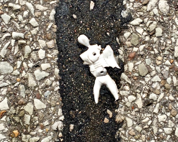 white plastic figure embedded in road tar